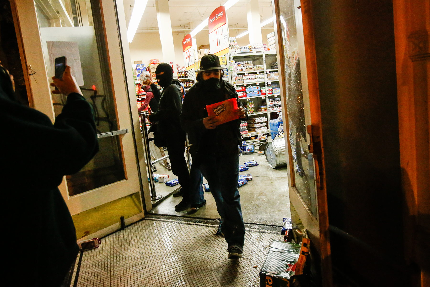A looter leaves a Smart & Final food and supply store during a demonstration following the grand jury decision in the Ferguson, Missouri shooting of Michael Brown, in Oakland, California November 25, 2014. The grand jury decided on Monday not to indict a white police officer over the fatal August shooting of an unarmed black teenager.