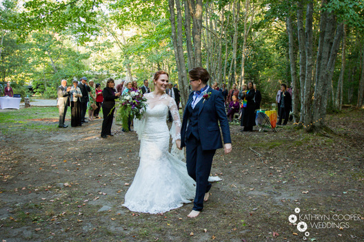 Barefoot wedding ceremony in Maine woods while camping at lesbian wedding