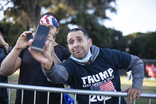 A Donald Trump supporter shows Joe Biden supporters a picture of Supreme Court judge Amy Coney Barrett, in Beverly Hills the day after President-elect Joe Biden won the election. Beverly Hills, Ca. November 8 2020