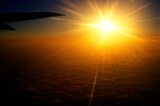 the sun setting seen thru the window of a commercial airliner.