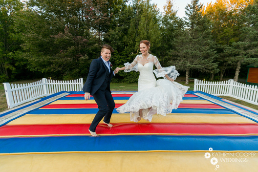 LGBT wedding photographer in Maine - destination photo of fun couple on bounce pad
