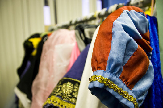 Costumes from past shows hang in an overfilled back room at the MTA studios in Newport Beach.