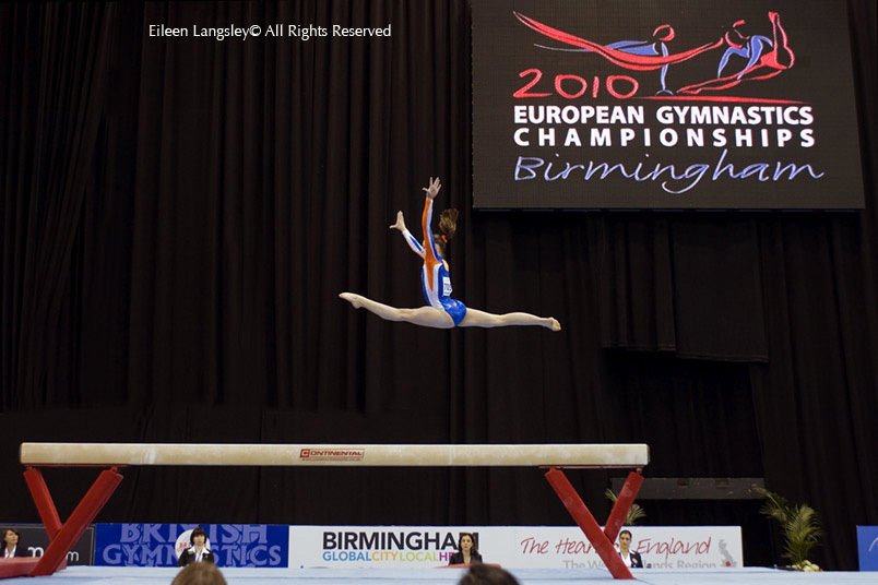 A wide angle generic image of a gymnast leaping on the beam at the 2010 European Gymnastics Championships in Birmingham
