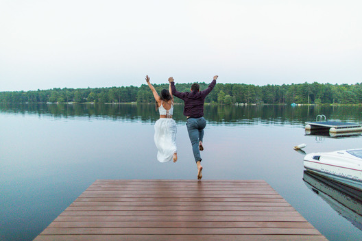 Creative wedding photographer capturing fun couple in Upstate NY as engaged couple jumps into lake with wedding dress on in Glen Spey