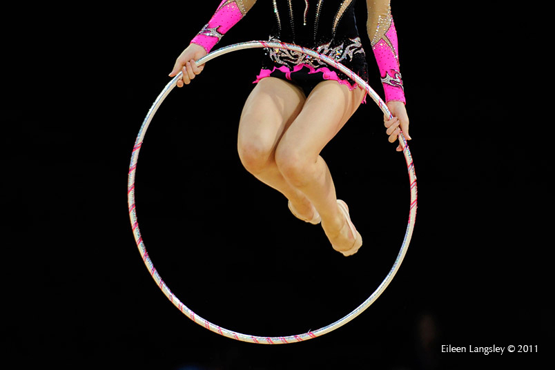 A cropped generic image of a gymnast jumping through the Hoop while competing at the World Rhythmic Gymnastics Championships in Montpellier