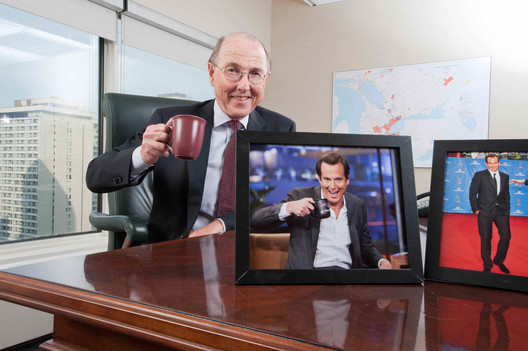 MACLEANS-ARNETT-03.19.12-TORONTO,ONTARIO: Chair of Hydro One Inc, James Arnett poses with a photo of his son; actor Will Arnett, at the Hydro One offices on Bay street, in Toronto, Ontario.