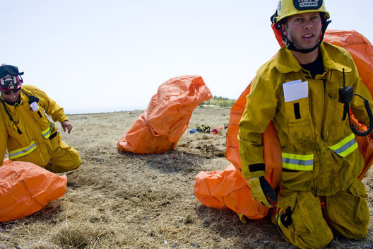 Newport Beach firefighter Adam Schwegman emerges from his protective fire shelter during Tuesday's wildfire refresher course.