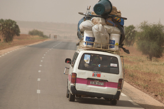 "Photo of a ""bush taxi"" on the two-lane, international highway from Ouagadougou, Burkina Faso to Niamey, Niger.  The taxi will stop anytime on the side of the road to let passengers on and collect new ones.  The 17-seater vehicle can be stuffed with up to 26 people."