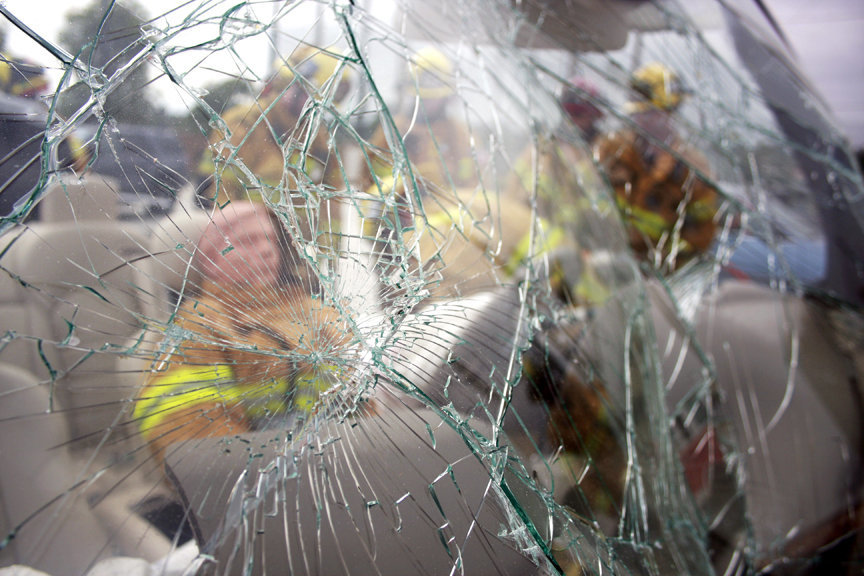 Firefighters work behind a cracked and rippled windshield during a training exercise on vehicle extrication.
