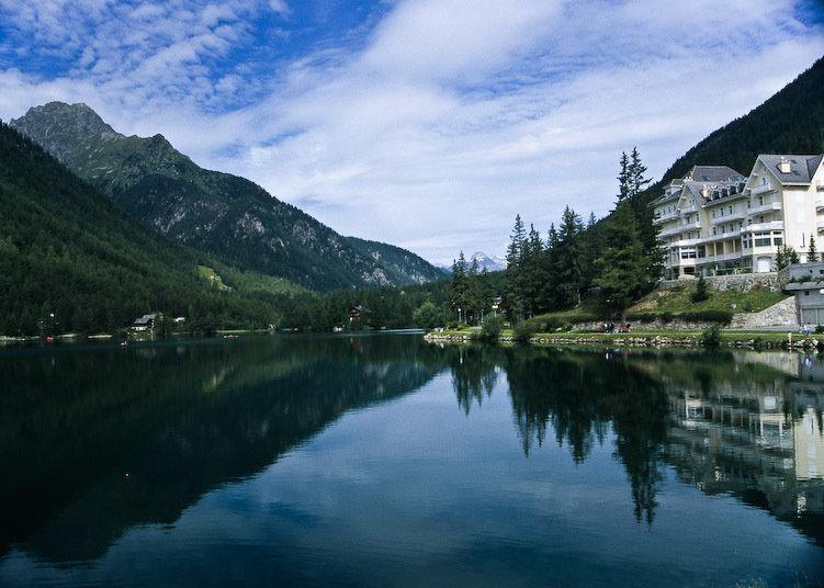 A lakeside mountain resort in the French Alps relfected into a lake in the foreground of the image and a mountain background
