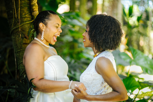 Destination elopement in Hawaii by elopement photographer Kathryn Cooper Weddings. A beautiful black lesbian couple laughs during their Big Island elopement.